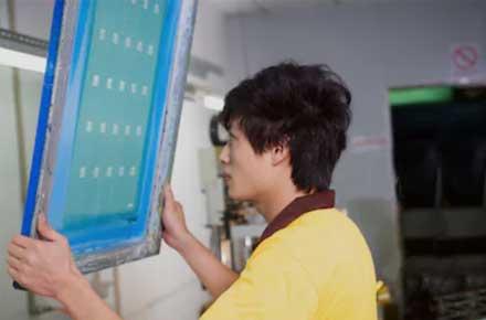 worker preparing silk screen block